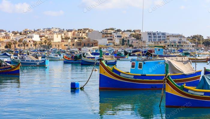 Marsaxlokk fishermen village in Malta. Traditional colorful boats at the port of Marsaxlokk