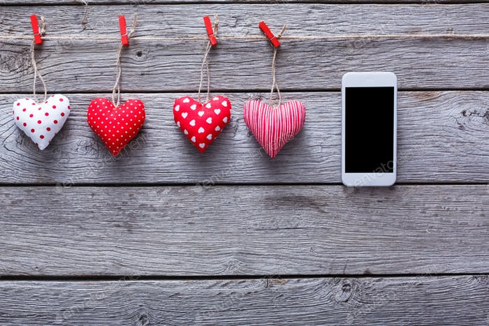 Valentine day background, pillow hearts and smartphone on wood