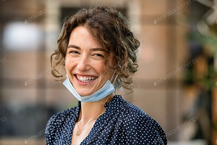 Happy woman laughing with face mask under chin