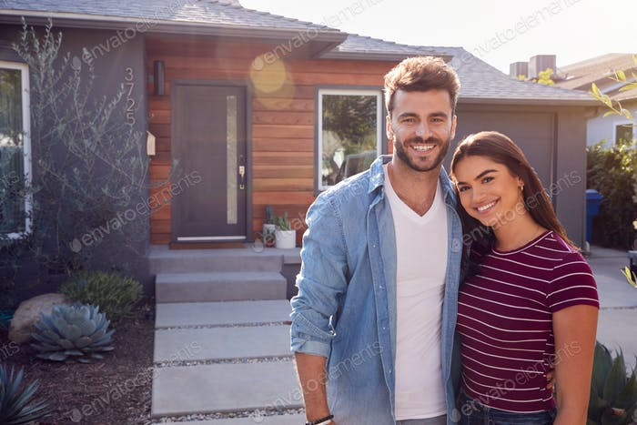 Portrait Of Couple Standing Outdoors In Front Of House With For Sale Sign In Garden