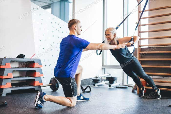 Woman exercising with personal trainer at the gym.