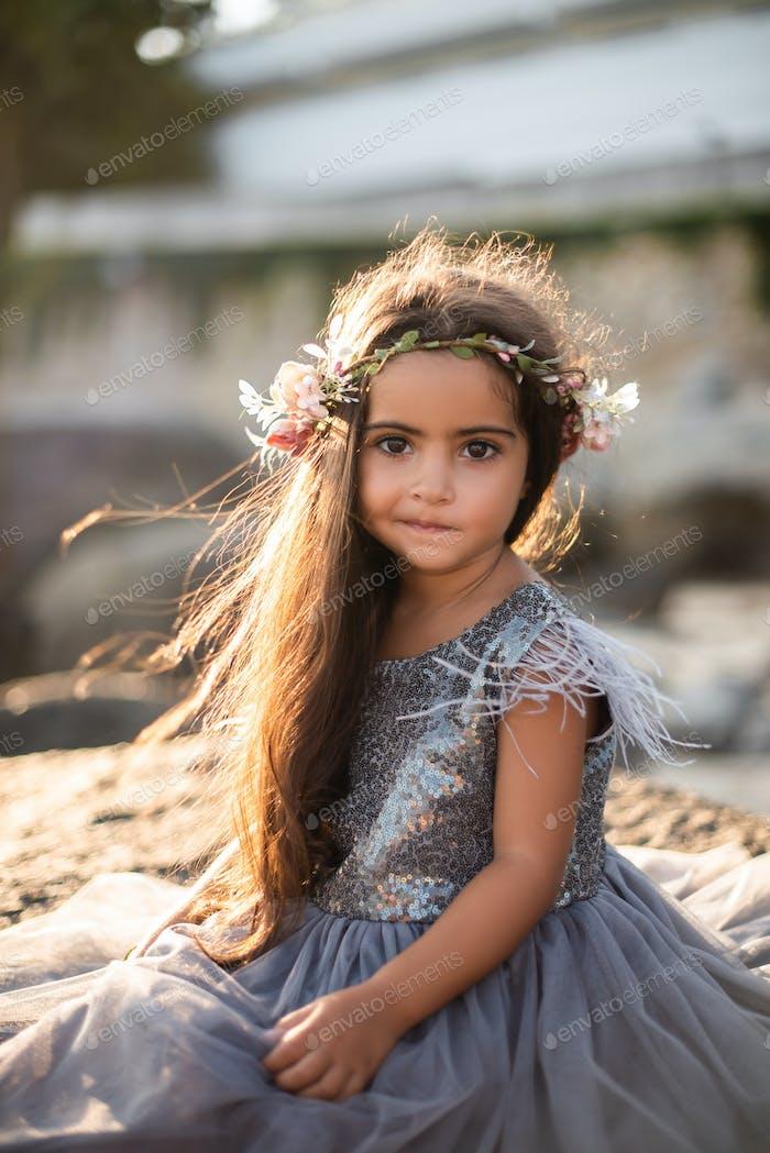 Fotografía cálida de niña que posa en la orilla durante el día