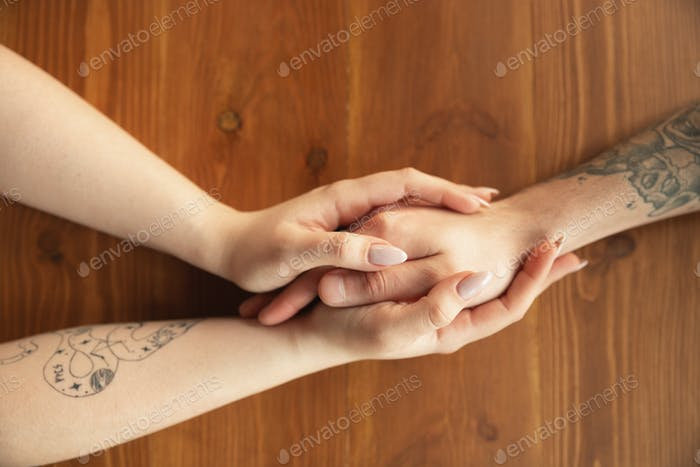 Loving couple holding hands close-up on wooden background, romantic