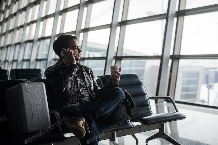Portrait of young handsome man wearing casual style clothes sitting on the bench in modern airport
