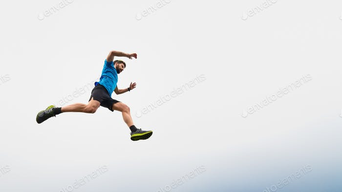 Athlete man running in the mountains during a jump