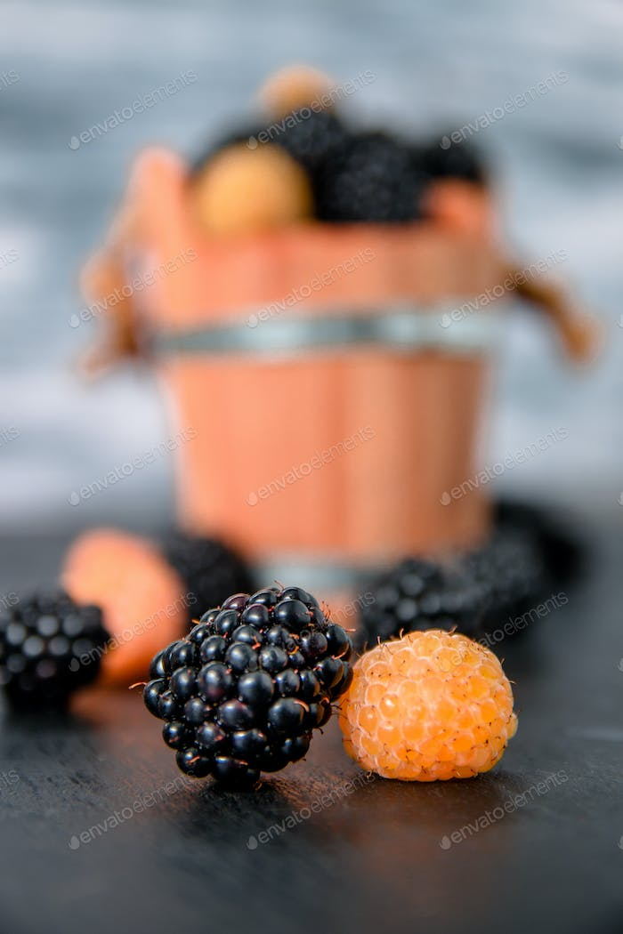 Close up of black and yellow raspberries on  table with basket  backround.