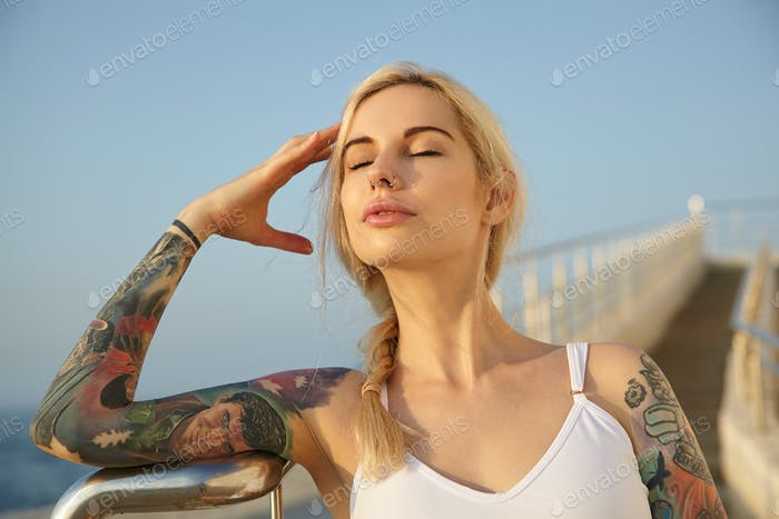 Close-up of beautiful tattooed young woman with long blonde hair combed in braid posing