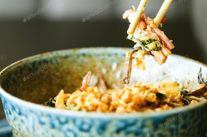 Die Hand des Mannes hält Essstäbchen über einem Teller japanischer, thailändischer, chinesischer Mahlzeit - Reis, Pilz