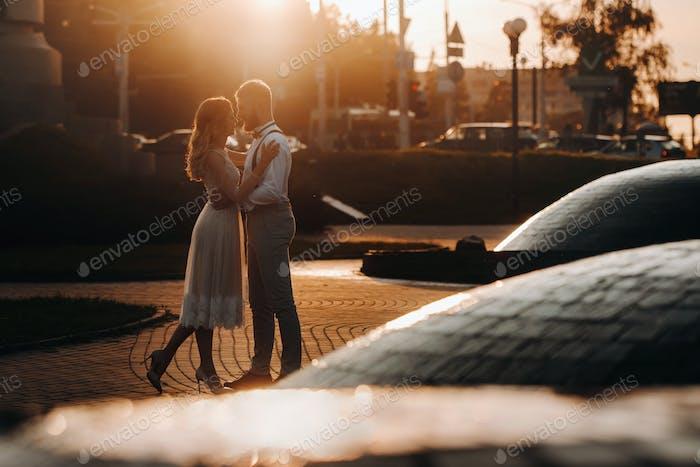 молодая пара обнимает в городе на красивом закате, урбанистическом стиле