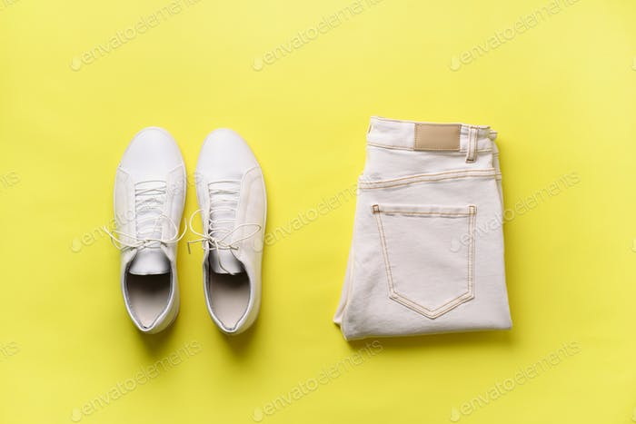 Female white sneakers and jeans on yellow background with copy space. Top view. Summer fashion