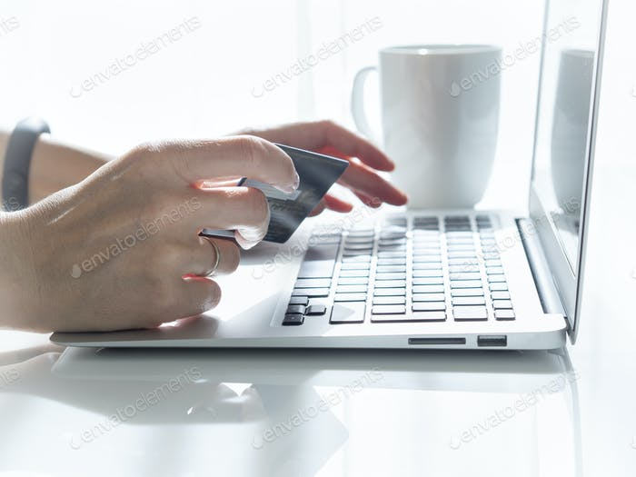 woman sitting at a table, drinking tea and looking at a laptop, pay for purchases