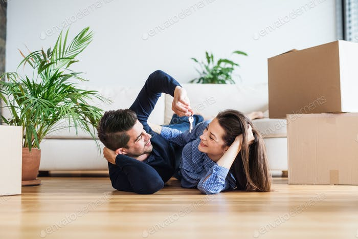 A young couple with a key and cardboard boxes moving in a new home.