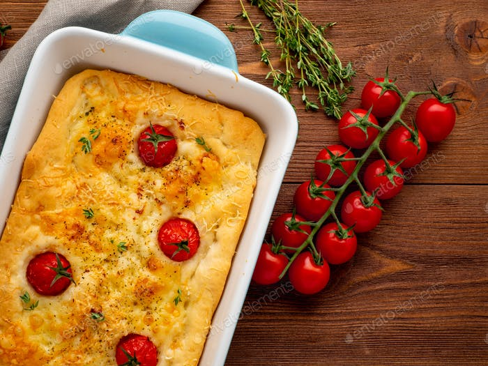 appetizing golden focaccia with tomatoes and spices, on dark wooden rustic table