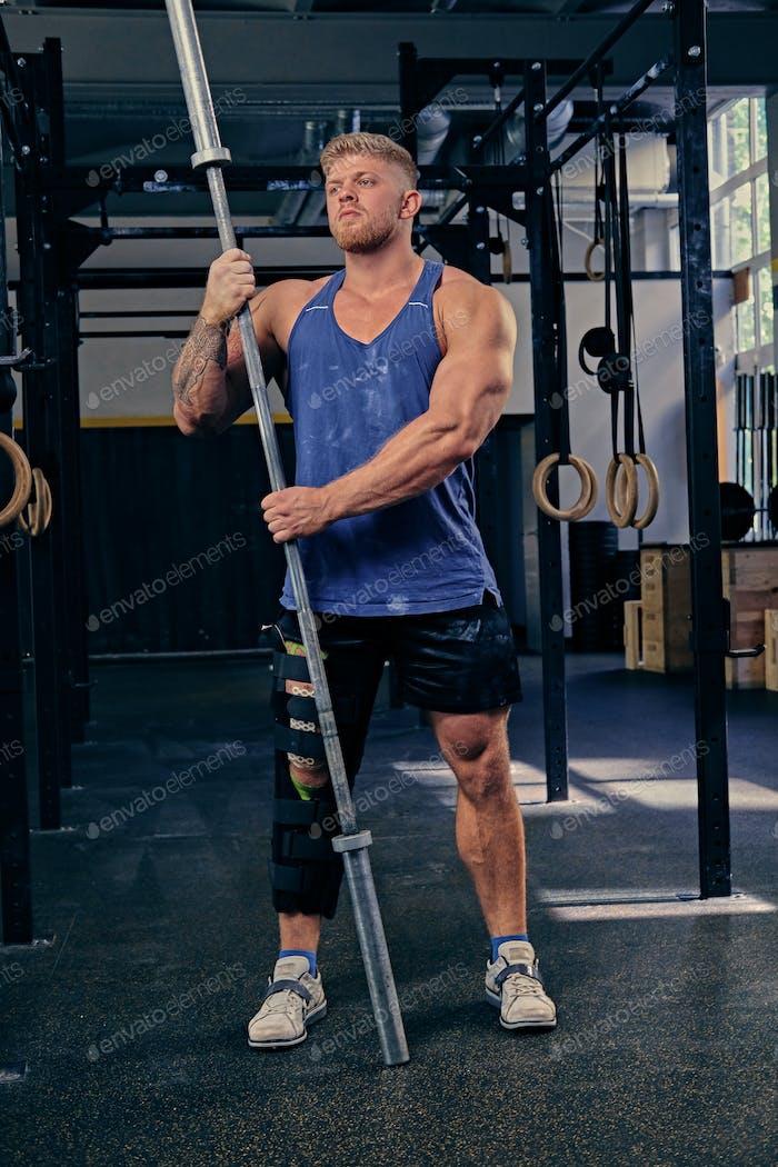 Bodybuilder with injured leg holds barbell.