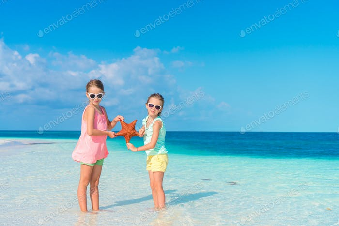 Adorable little girls holding giant red starfish