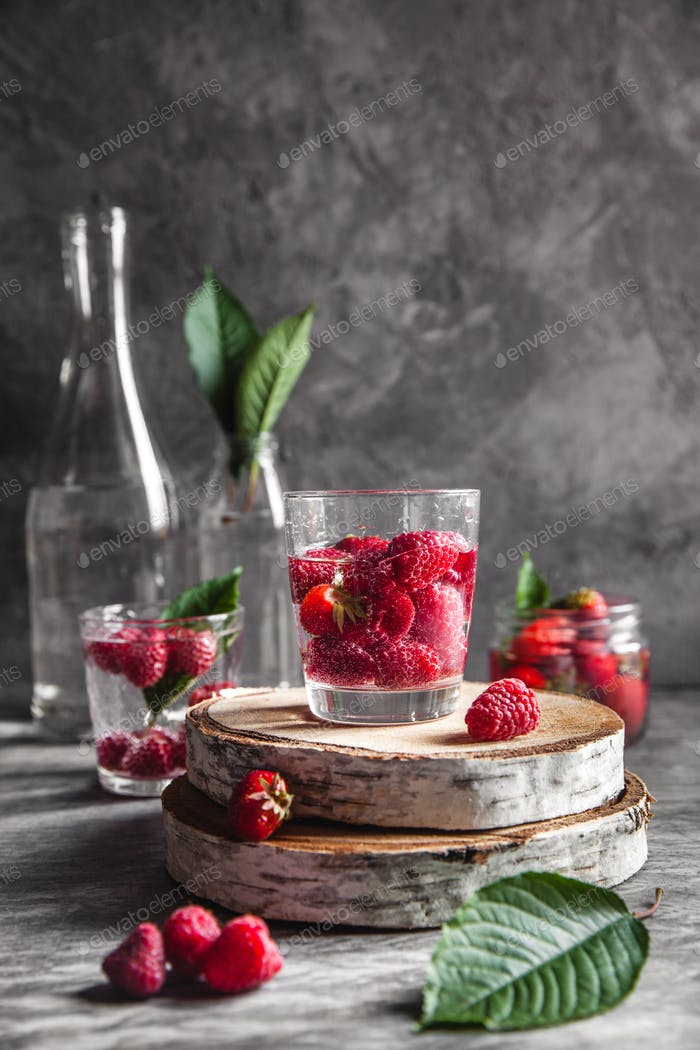 Strawberries in water on a dark gray background. Healthy food, fruit