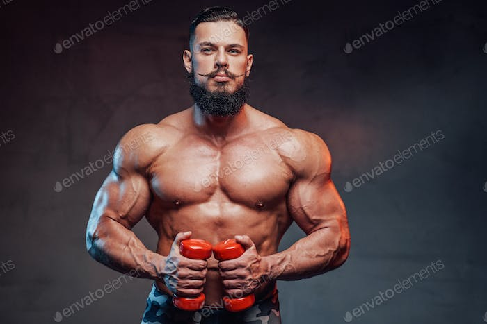 Muscular guy with beard holding dumbells and posing in studio