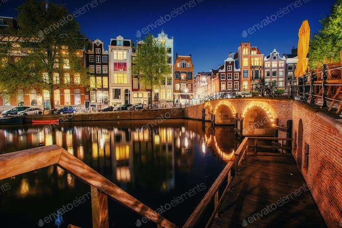 Kanal in Amsterdam in der Nacht. Hervorhebung von Gebäuden und Straßen