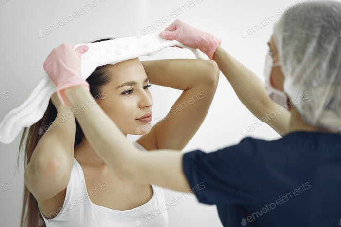 Woman with a doctor in cosmetology studio