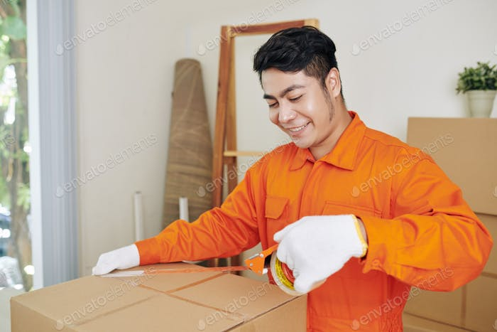 Smiling worker sealing boxes