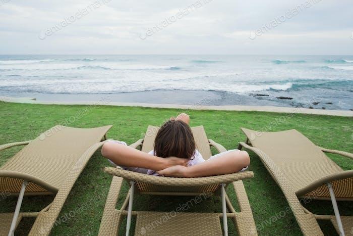 caucasian woman relaxing in chair near indian ocean in Srilanka.