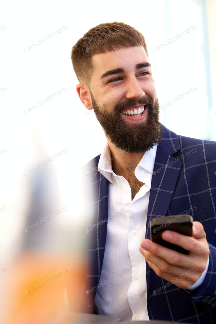 Close up happy businessman holding mobile phone