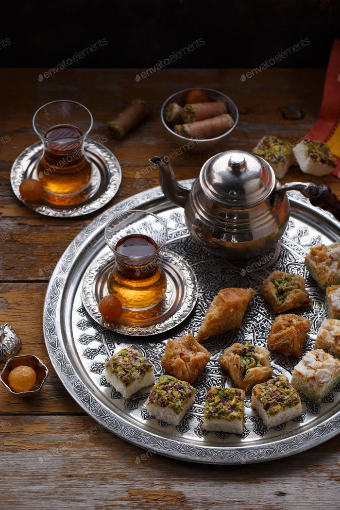 Assorted oriental sweets with tea in traditional cups, copy space