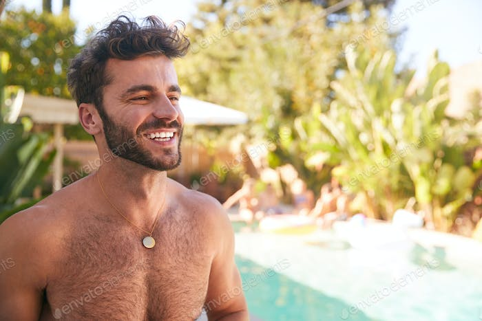 Portrait Of Bare Chested Hispanic Man Outdoors With Friends Enjoying Summer Pool Party