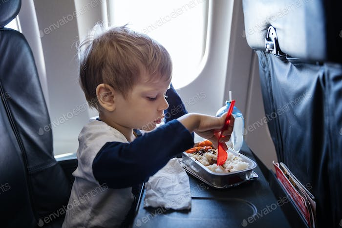 Little boy having a meal on board of a plane