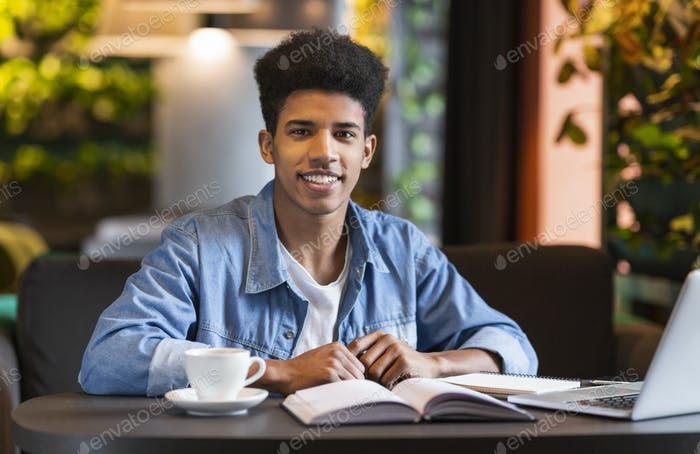 Cheerful black student doing homework at cafe