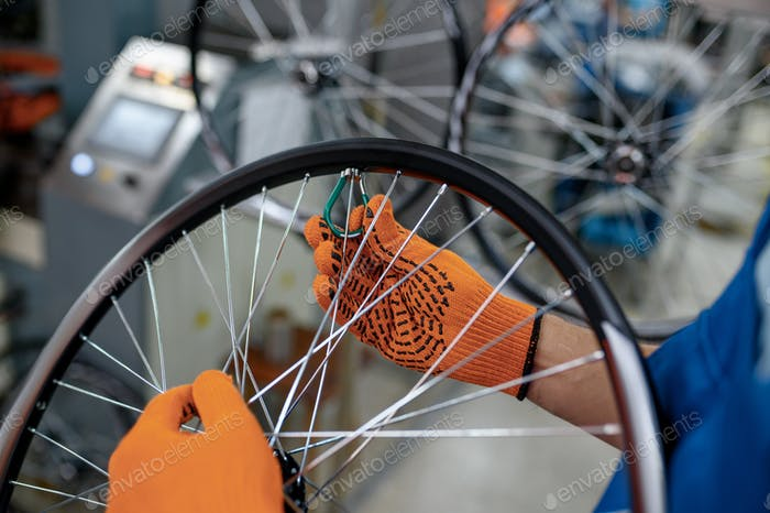 Worker in gloves installs bicycle spokes, factory
