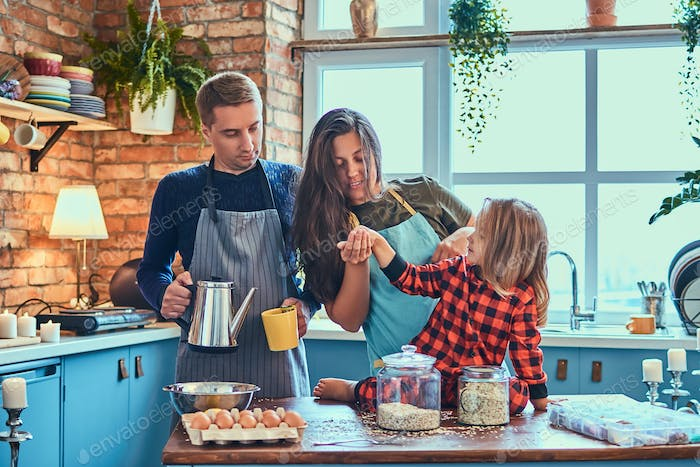 Family together cooking breakfast in loft style kitchen.