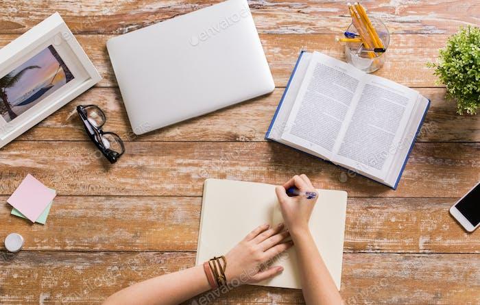 Hände mit Buch Schreiben auf Notizbuch am Tisch