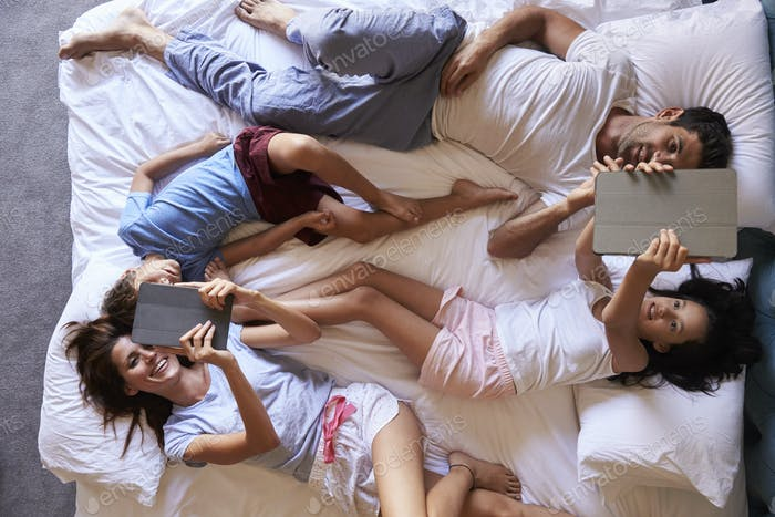Overhead View Of Family Lying On Bed Using Digital Tablets