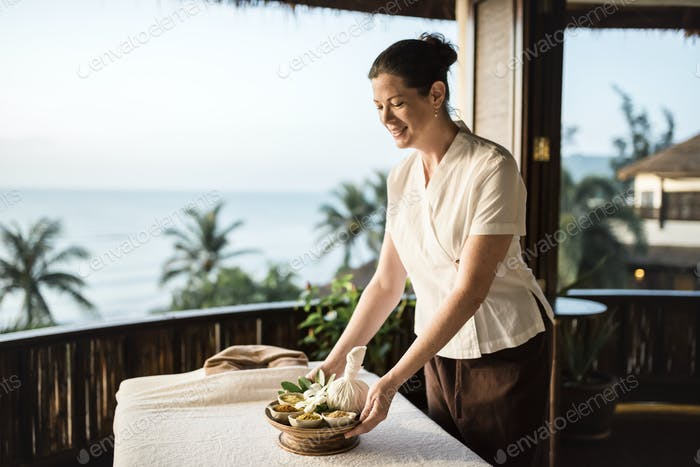 Masseuse preparing massage table