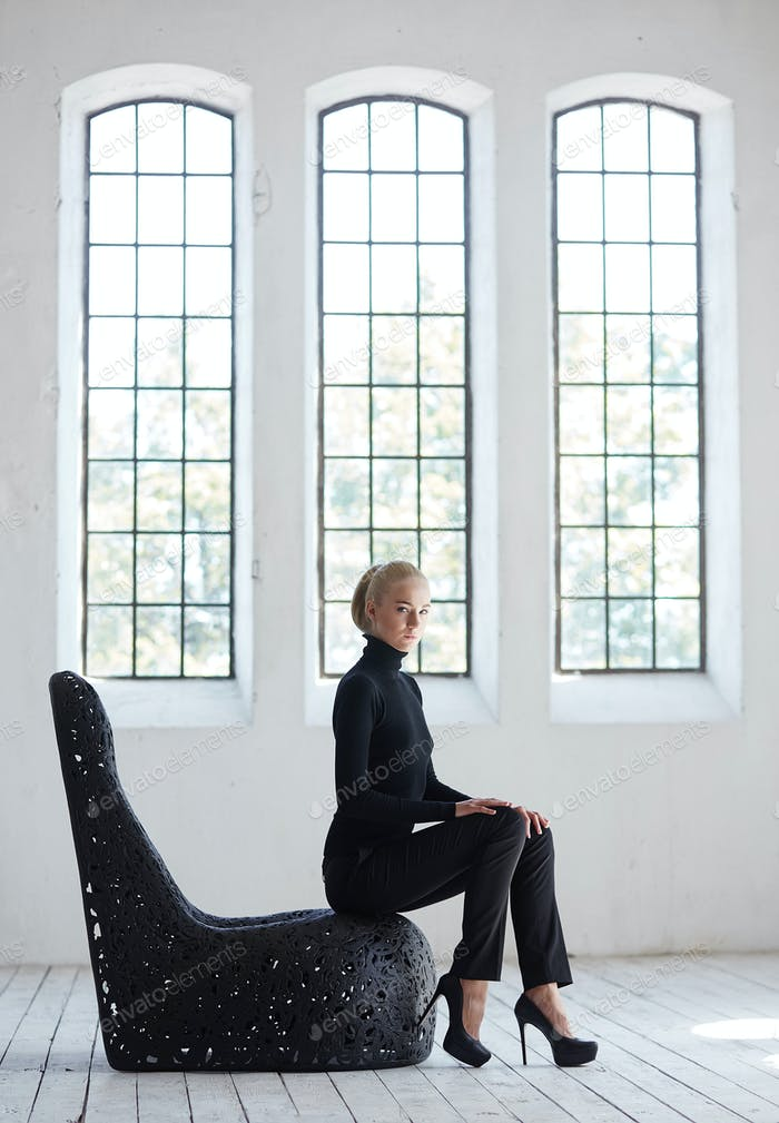 Female in a black costume sits on a round black.