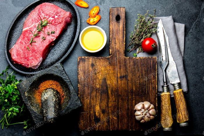 Frisches rohes Fleisch Steak Rinderfilet, Kräuter und Gewürze rund um das Schneidebrett.