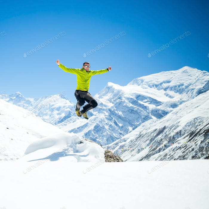 Happy man jumping success in mountains