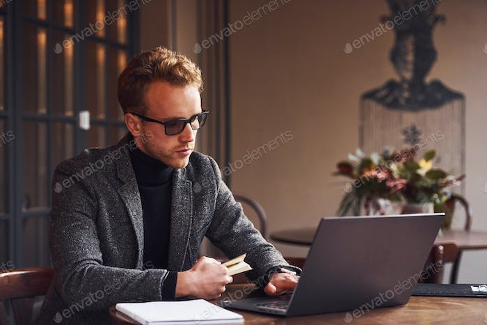 Elegant young guy in formal wear sits in cafe with his laptop and credit card in hand