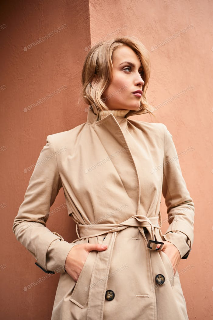 Side view of serious casual blond girl in beige trench coat confidently looking away outdoor