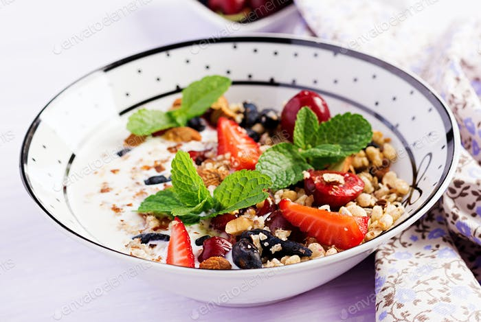 Healthy breakfast - granola, strawberries, cherry, honeysuckle berry, nuts and yogurt in a bowl.