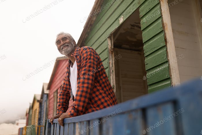 Low angle view of happy senior man looking away while standing at beach hut on a sunny day