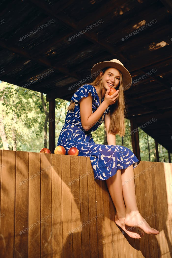 Smiling girl in dress and hat barefoot happily looking in camera eating peaches on wooden fence