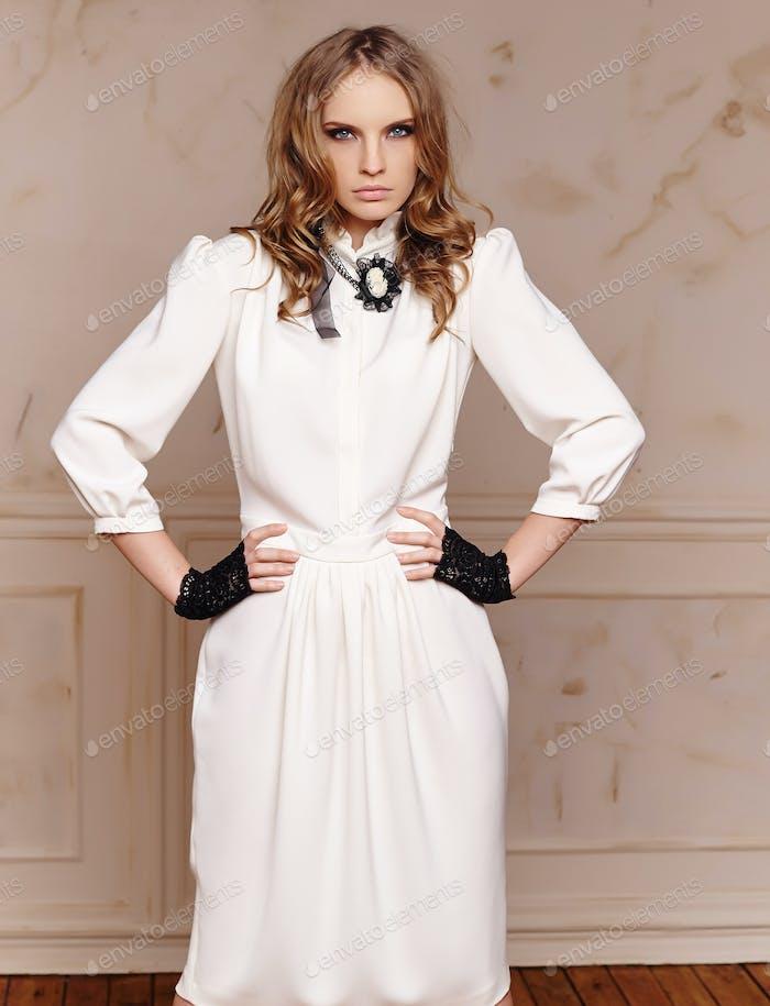 Porträt der modernen Frau in weißem Kleid und schwarzen Handschuhen.