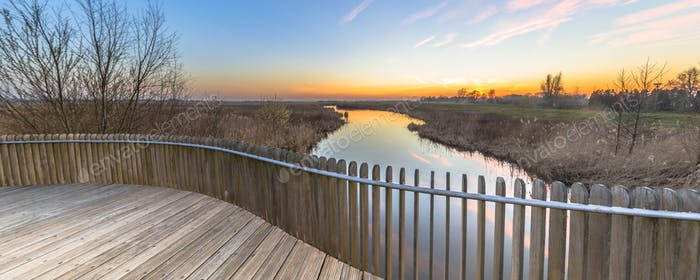 Wooden balustrade sunset over swamp