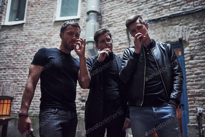 Gemeinsam rauchen. Drei männliche Freunde stehen vor der Bar. Konversation haben. In schönen Kleidern