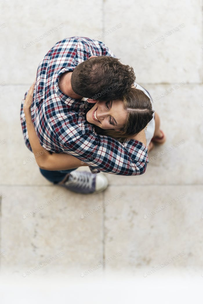 Young loving couple hugging in the street. From top view.