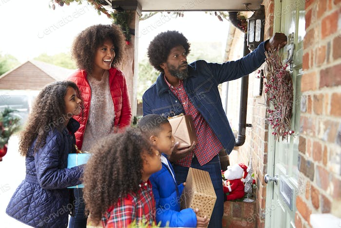 Family Knocking On Front Door As They Arrive For Visit On Christmas Day With Gifts