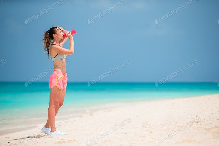 Fit young woman doing exercises on tropical white beach in her sportswear