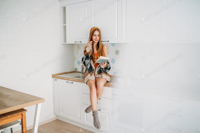 Beautiful smiling girl wearing in cozy knitted cardigan reading book on kitchen table at home